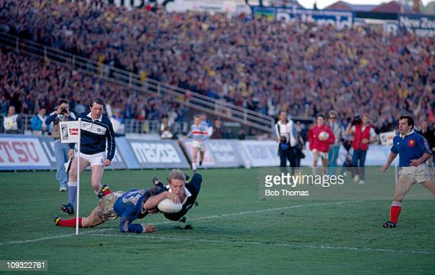 New Zealand wing John Kirwan dives past Philipe Sella of France to score a Try during the Rugby Union World Cup Final held in Auckland on 20th June...