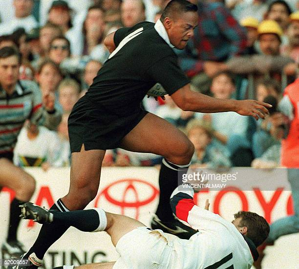New Zealand winger Jonah Lomu runs through England's fullback Mike Catt during the Rugby World Cup semifinal match between New Zealand and England 18...