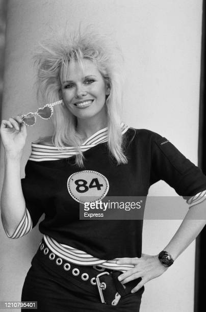 New Zealandborn actress and writer Pamela Stephenson poses holding a pair of heartshaped sunglasses and wearing a top with a circular emblem on which...