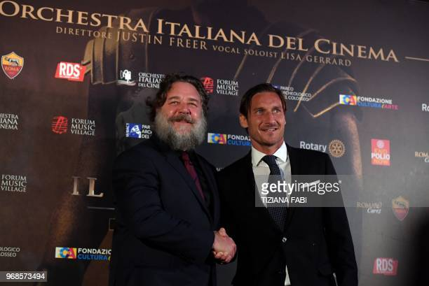 New Zealander actor Russell Crowe poses with AS Roma's former player Francesco Totti at the Colosseum in Rome before the charity screening of the...