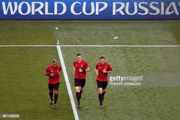 New Zealander referee Matt Conger runs with New Zealander assistant referee Simon Lount and Tongan assistant referee Tevita Makasini ahead of the...