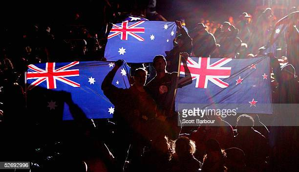 New Zealanders and Australians hold their national flags aloft during the dawn ceremony to mark the 90th anniversary of the landing of soldiers on...