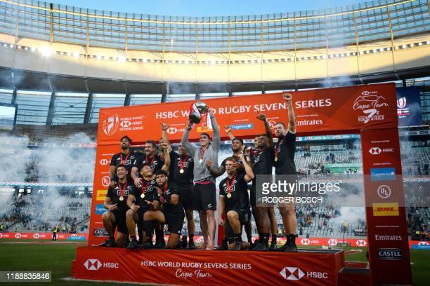 New Zealand's 7s rugby team celebrates on the podium with the trophy after winning the World Rugby Sevens Series men's final rugby match between New...