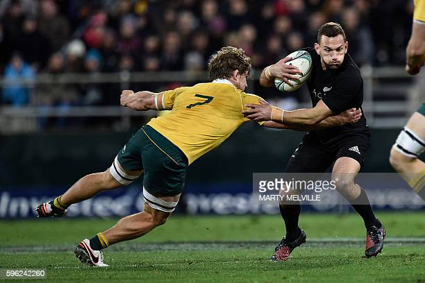 New Zealand's Aaron Cruden is tackled by Australia's Michael Hooper during the rugby Test match between New Zealand and Australia at Westpac Stadium...