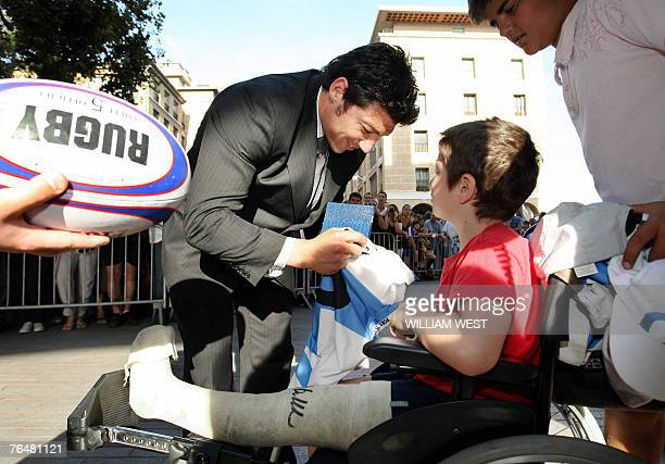 New Zealand's All Black halfback Byron Kelleher signs an autograph for a boy with a broken leg in Marseille 02 September 2007 The All Blacks who are...