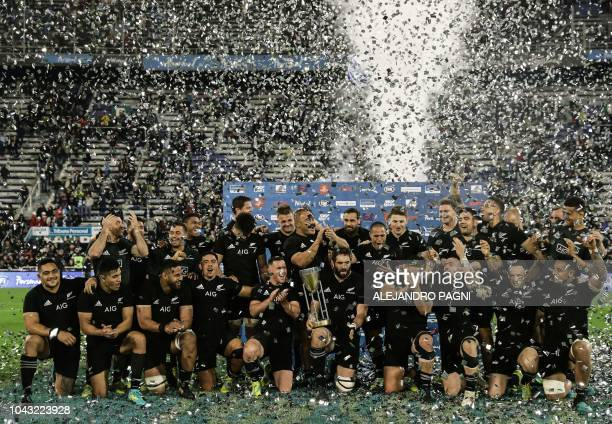 New Zealand's All Blacks players celebrate with the trophy after winning the Rugby Championship 2018 edition after defeating 3517 to Argentina's Los...