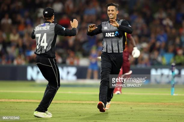 New Zealand's Anaru Kitchen celebrates with Mitchell Santner after taking the wicket of West Indies batsman Rovman Powell during the third Twenty20...