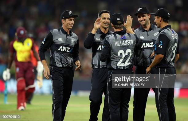New Zealand's Anaru Kitchen celebrates with teammates after taking the wicket of West Indies batsman Rovman Powell during the third Twenty20...