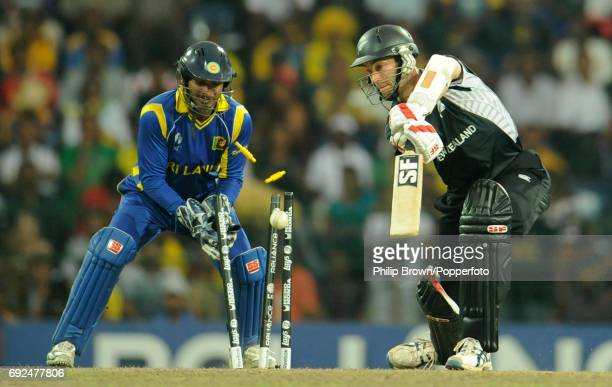 New Zealand's Andy McKay is bowled by Sri Lanka's Ajantha Mendis as Sri Lanka's captain and wicketkeeper Kumar Sangakkara looks on during their ICC...