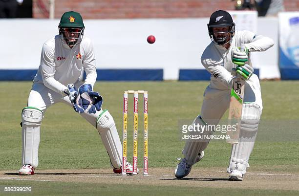 New Zealand's batsman Martin Guptill plays a shot as Zimbabwe's wicket keeper PJ Moor looks on during the first day of the second test in a series of...
