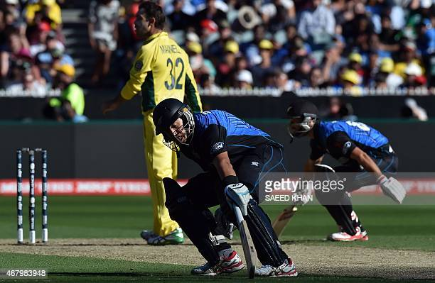 New Zealand's batsmen Ross Taylor and Grant Elliott complete their run as Australia's spin bowler Glenn Maxwell walks back to his bowling mark during...