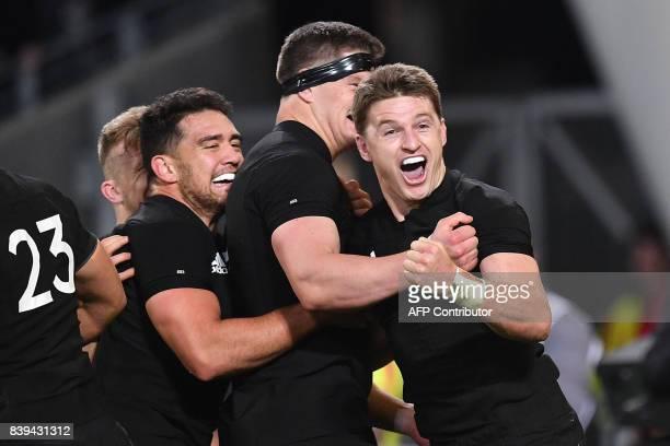 TOPSHOT New Zealand's Beauden Barrett celebrates a try with teammates Anton LienertBrown and Scott Barrett during the second Bledisloe Cup match...