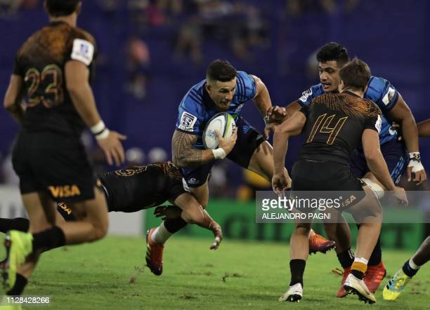 New Zealand's Blues fullback Sonny Bill Williams is tackled by Argentina's Jaguares centre Matias Moroni during a Super Rugby match at Jose...