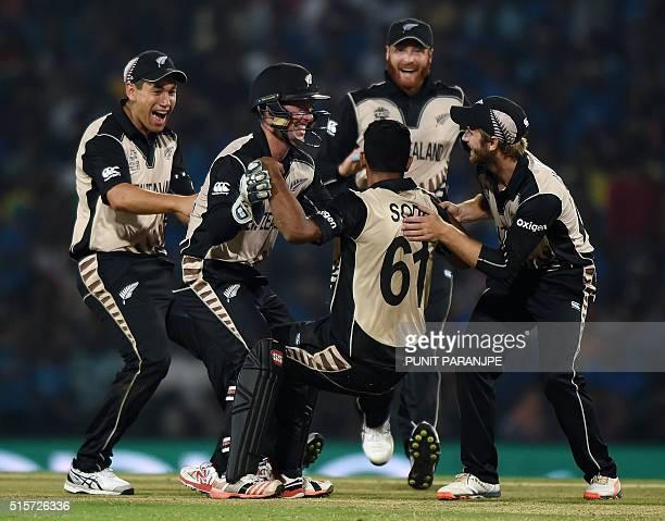New Zealand's bowler Ish Sodhi celebrates with teammates after taking the wicket of India's batsman Ravindra Jadeja during the World T20 cricket...