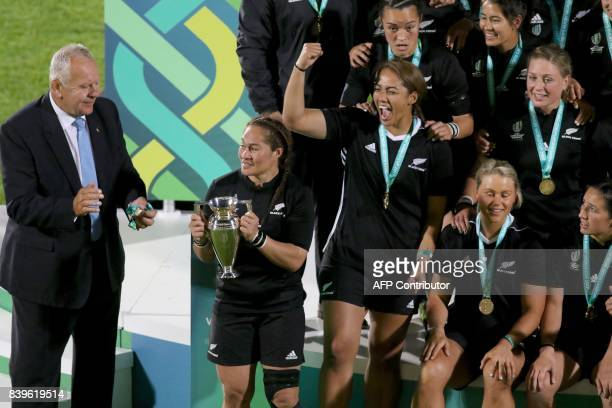 New Zealand's captain Fiao'o Faamausili receives the cup from Chairman of world rugby, Bill Beaumont as New Zealand's players celebrate their victory...