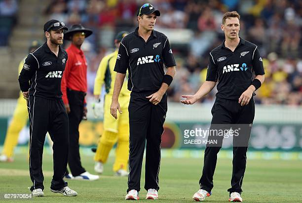 New Zealand's captain Kane Williamson and Tim Southee talk to paceman Matt Henry after consecutive boundaries hit by Australia's batsman Mitchell...