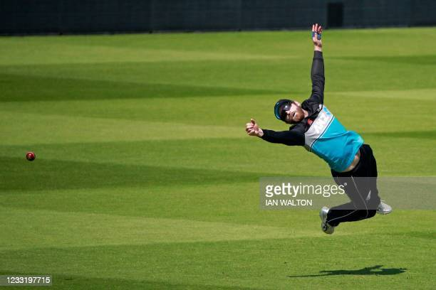 New Zealand's captain Kane Williamson dives for the ball in the slips during a training session at Lord's Cricket Ground in London on May 31, 2021...