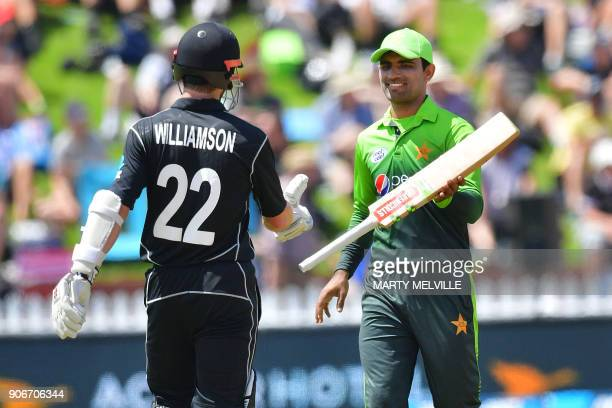 New Zealand's captain Kane Williamson his handed his bat by Pakistan's Fakhar Zaman after it was knocked out of his hand by a shot from team mate...