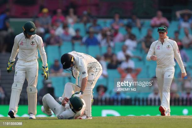 New Zealands captain Tom Latham consoles Australia's Matthew Wade after he was hit on the helmet while fielding during the second day of the third...