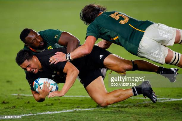 TOPSHOT New Zealand's centre Anton LienertBrown is tackled by South Africa's prop Tendai Mtawarira and lock Franco Mostert during the Japan 2019...