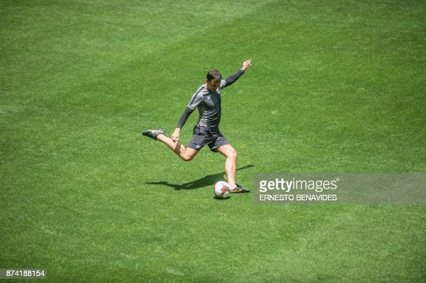 New Zealand's coach Anthony Hudson kicks a ball during a training session in Lima on November 14 2017 on the eve of the second leg match of their...