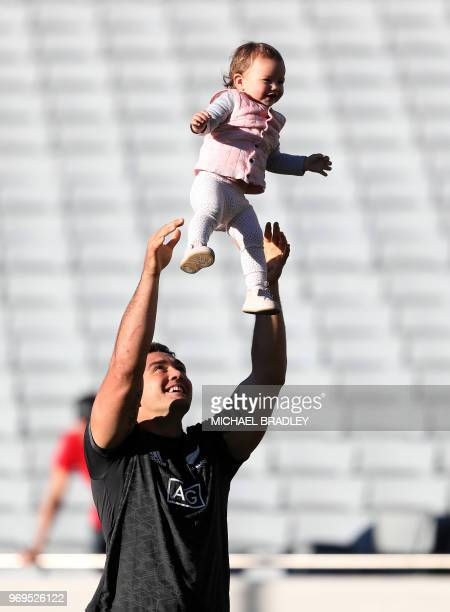 New Zealand's Codie Taylor shares a moment with his daughter during the captain's run training session at Eden Park in Auckland on June 8 ahead of...