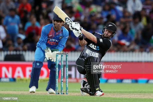 New Zealand's Colin Munro plays a shot as India's MS Dhoni looks on, during the third Twenty20 international cricket match between New Zealand and...