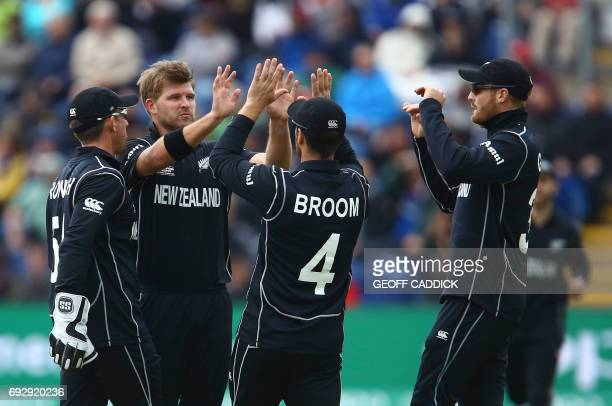 New Zealand's Corey Anderson celebrates with teammates after taking the wicket of England's Joe Root during the ICC Champions Trophy match between...
