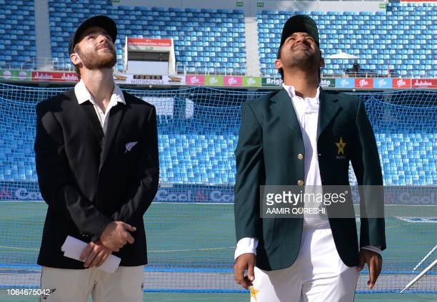 New Zealand's cricket captain Kane Williamson and his Pakistani counterpart Sarfraz Ahmed watch the coin during the toss prior to the start of the...