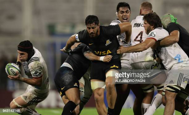 New Zealand's Crusaders flanker Matt Tood runs with the ball past Argentina's Jaguares players during their Super Rugby match at Jose Amalfitani...