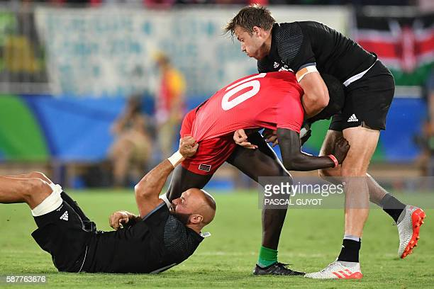 TOPSHOT New Zealand's D J Forbes and New Zealand's Tim Mikkelson tackle Kenya's Bush Mwale in the mens rugby sevens match between New Zealand and...