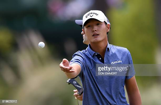 New Zealand's Danny Lee thows a ball to his caddie during Round 1 of the 80th Masters Golf Tournament at the Augusta National Golf Club on April 7 in...