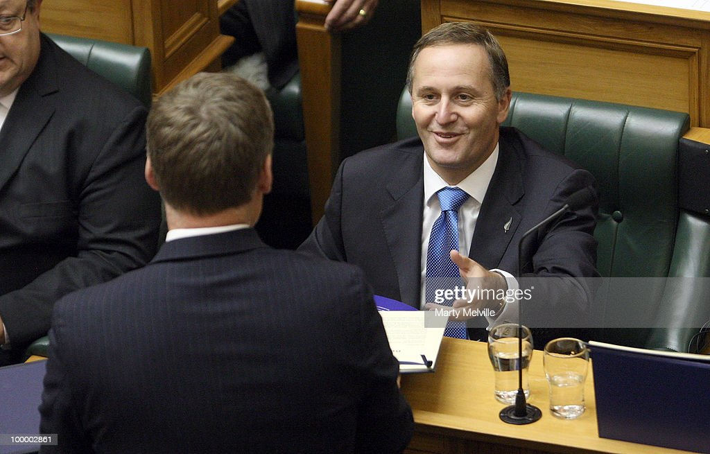 New Zealand's Finance Minister Bill English hands a copy of the budget to Prime Minister of New Zealand John Key before the reading of the Budget in Parliament House on May 20, 2010 in Wellington, New Zealand. English announced tax cuts across the board, with all income tax rates to be cut from October this year and company tax rates from April next year.