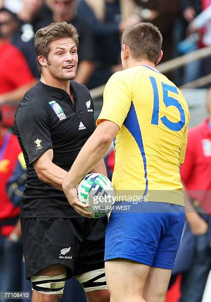 New Zealand's flanker and captain Richie McCaw conforts Romania's fullback Iulian Dumitras during the rugby union World Cup group C match New Zealand...