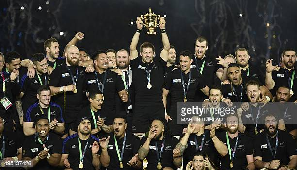New Zealand's flanker and captain Richie McCaw holds the Webb Ellis Cup as he celebrates with teammates after winning the final match of the 2015...