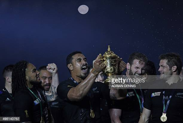 New Zealand's flanker Jerome Kaino holds the the Webb Ellis Cup as he celebrates with teammates after winning the final match of the 2015 Rugby World...