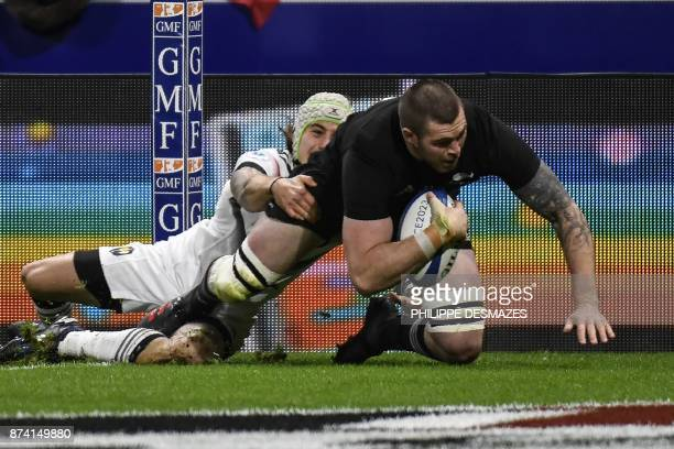New Zealand's flanker Liam Squire scores a try against France's right wing Gabriel Lacroix during the international rugby union test match between...