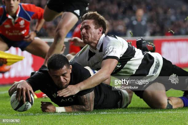 New Zealand's flanker Vaea Fifita dives over the line to score their second try during the international rugby union match between Barbarians and New...