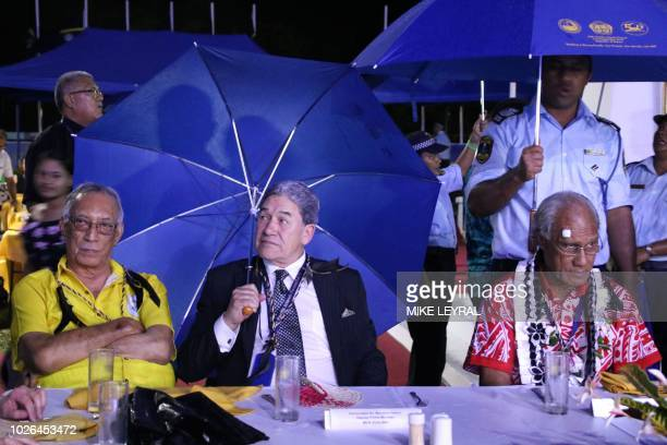 New Zealand's Foreign Minister Winston Peters shields himself from the rain with an umbrella during the opening ceremony of the Pacific Islands Forum...