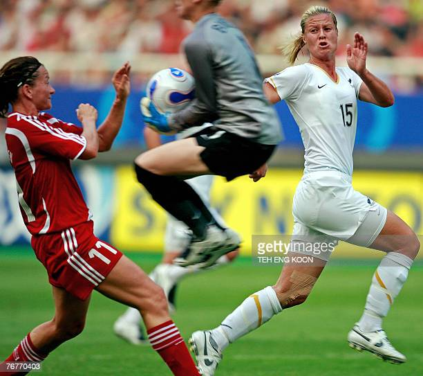 New Zealand's Goalkeeper Jenny Bindon catches the ball as Denmark's Forward Merete Pedersen and New Zealand's Defender Maia Jackman run past during...