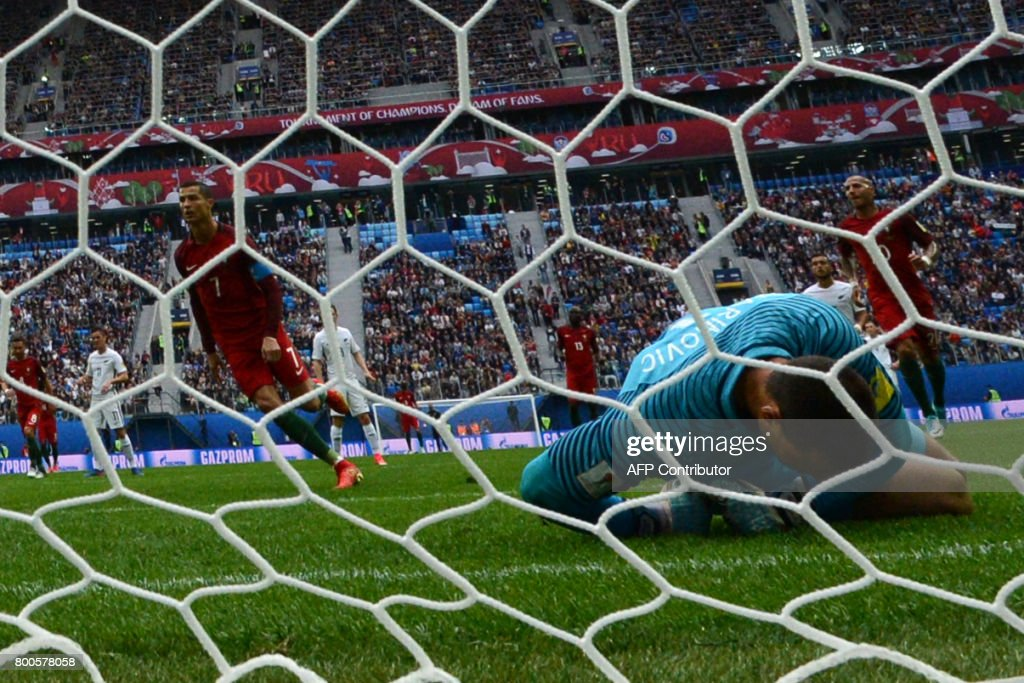 New Zealand's goalkeeper Stefan Marinovic (R) reacts after failing to save a penalty kicked by Portugal's forward Cristiano Ronaldo (C) during the 2017 Confederations Cup group A football match between New Zealand and Portugal at the Saint Petersburg Stadium in Saint Petersburg on June 24, 2017. / AFP PHOTO / Mladen ANTONOV