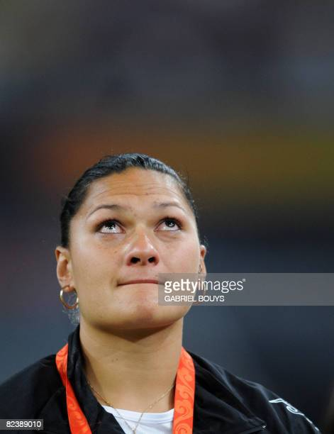 New Zealand's gold medalist Valerie Vili cries as she poses on the podium a day after the women's shot put at the National Stadium as part of the...