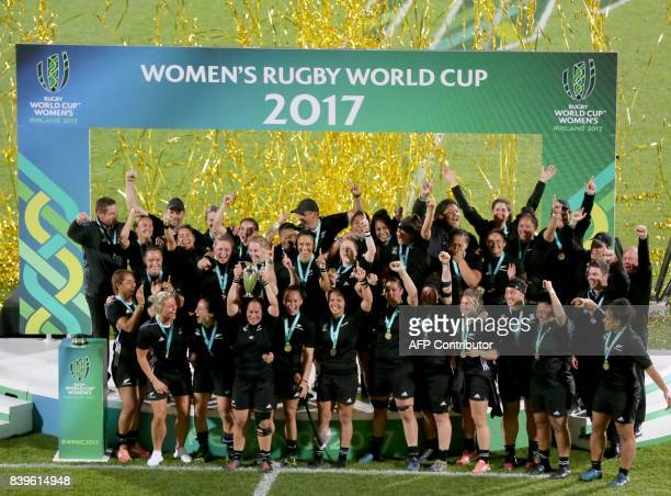 New Zealand's hooker Fiao'o Faamausili lifts the cup as New Zealand's players celebrate their victory on the pitch after the Women's Rugby World Cup...