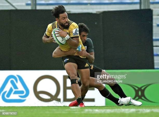 New Zealand's Hurricanes centre Matt Proctor is tackled by Argentina's Jaguares centre Matias Orlando during their Super Rugby match at Jose...