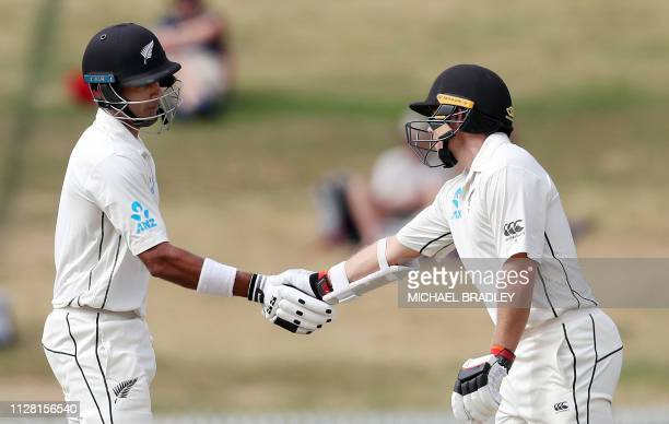 New Zealand's Jeet Raval and Tom Latham shake hands during day two of the first cricket Test match between New Zealand and Bangladesh at Seddon Park...