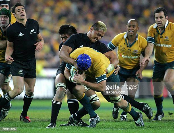 New Zealand's Jerry Collins , tackles Australia's Nathan Sharpe , during the Bledisloe Cup rugby match against Australia in Sydney, 13 August 2005....