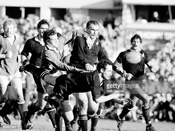 New Zealand's Jock Hobbs passes the ball despite being tackled by British Lion's fullback Gwyn Evans whilst All Black Andy Haden tries to help Hobbs...