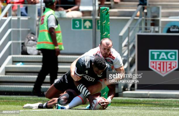 New Zealand's Joe Ravouvou scores a try against England during their match on the second day of the World Rugby Sevens Series at Cape Town Stadium in...
