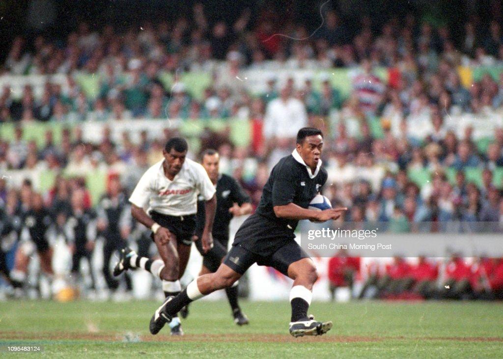 New Zealand's Jonah Lomu (in black) sprint pass the Fijian defence during the Cup final of Hong Kong Sevens at Hong Kong Stadium. 26 March 1995 : News Photo