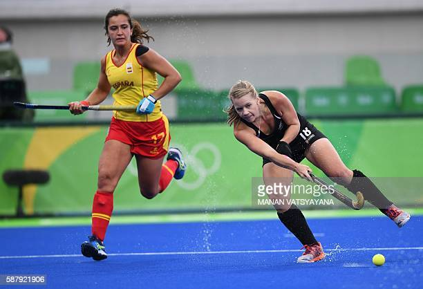 New Zealand's Kirsten Pearce hits the ball as Spain's Lola Riera looks on during the women's field hockey Spain vs New Zealand match of the Rio 2016...